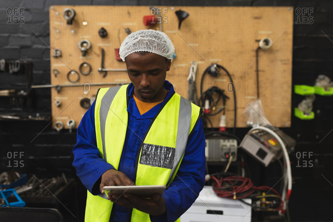 Front view close up of a young African American male factory worker using a tablet computer in the machine shop at a processing plant, with equipment and tools in the background