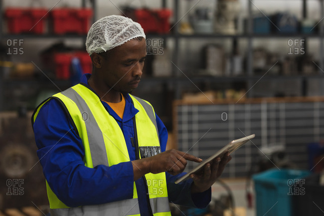 Side view close up of a young African American male factory worker using a tablet computer in the machine shop at a processing plant, with equipment and tools in the background