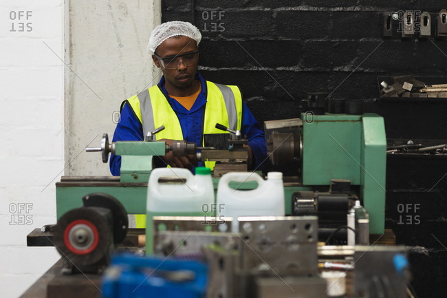 Front view close up of a young African American male factory worker sitting and operating equipment in the machine shop at a processing plant, with equipment and tools in the foreground