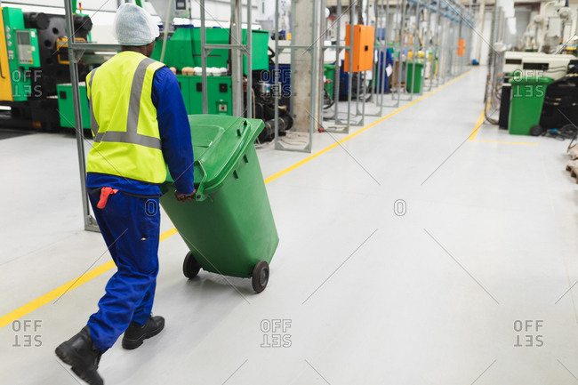 Rear view close up of a young African American male factory worker wheeling a green bin through a warehouse at a processing plant