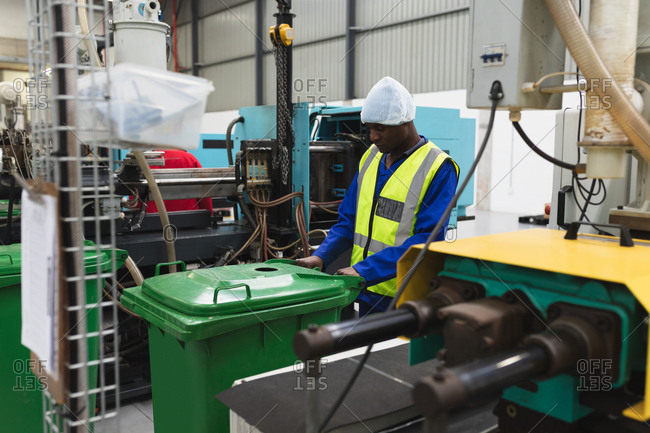 Side view close up of a young African American male factory worker moving a green in a warehouse at a processing plant, surrounded by equipment and machinery