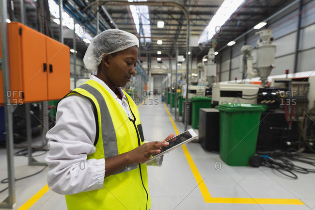 Side view close up of a young African American female factory worker standing using a tablet computer in a warehouse at a processing plant