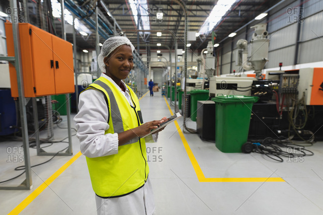 Side view close up of a young African American female factory worker standing using a tablet computer and smiling to camera in a warehouse at a processing plant
