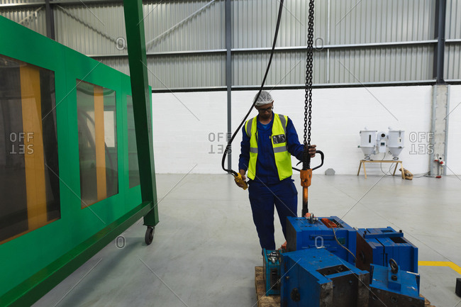 Front view of a middle aged mixed race male factory worker wearing glasses and workwear moving machine parts on a trolley and operating a lifting chain in a loading area in a warehouse at a processing plant