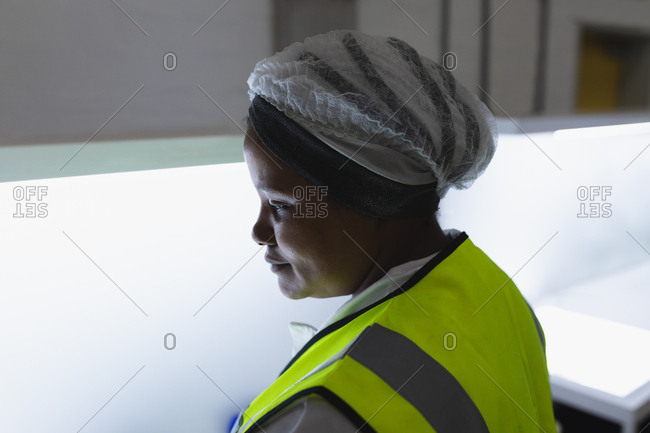 Side view close up of a young African American female factory worker inspecting equipment in a warehouse at a factory
