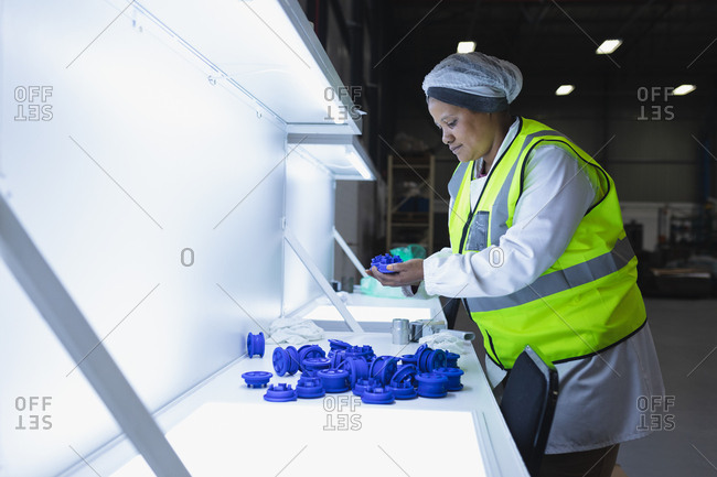 Side view close up of a young African American female factory worker inspecting plastic parts under bright light in a warehouse at a factory