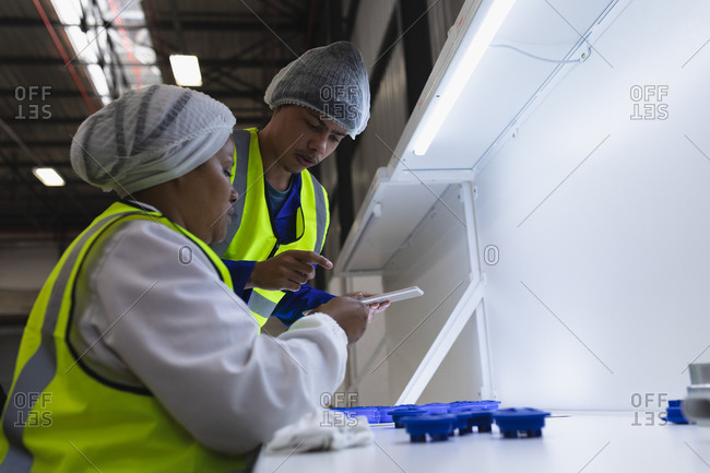 Side view close up of a young mixed race male factory worker using a tablet computer talking with a young African American female factory worker sitting and inspecting plastic parts under bright light in a warehouse at a factory