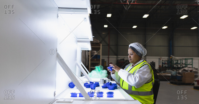Side view of a young African American female factory worker sitting and inspecting plastic parts under bright light in a warehouse at a factory