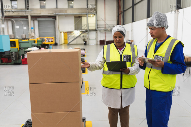 Front view close up of a young mixed race female and a young mixed race male factory worker talking in a warehouse loading bay at a factory. The woman is pointing to a stack of boxes and holding a clipboard, the man is using a tablet computer, both are dressed in workwear