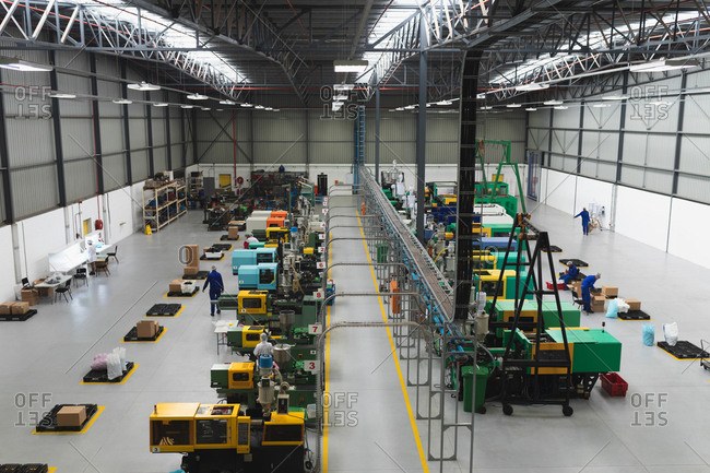 High angle view of two rows of processing equipment and the packing area in a warehouse at a processing plant, with factory workers visible working in the background