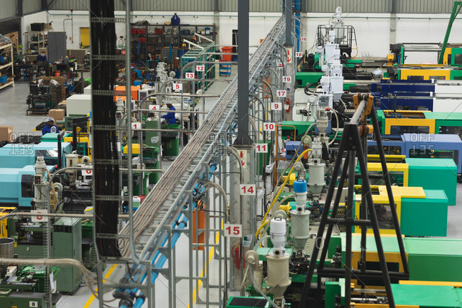 High angle view of factory workers operating machines in a warehouse at a factory processing plant