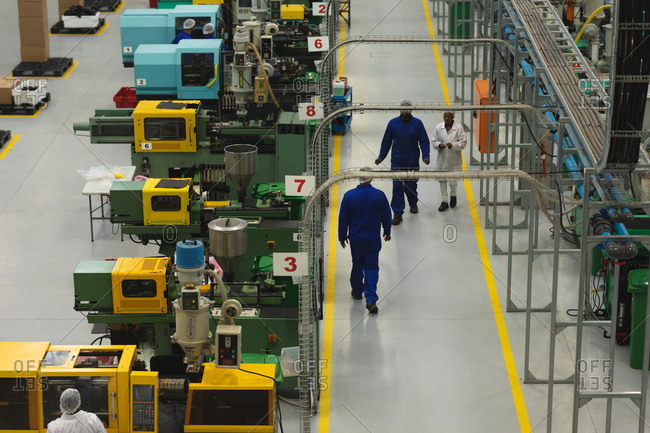High angle view of factory workers interacting and walking past rows of machines in a warehouse at a factory processing plant