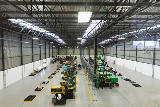 High angle view of factory workers operating machines and interacting in a warehouse at a factory processing plant