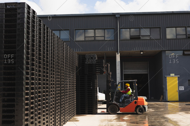 Side view of a middle aged Caucasian male factory worker using a forklift truck to move a stack of pallets outside a warehouse at a factory