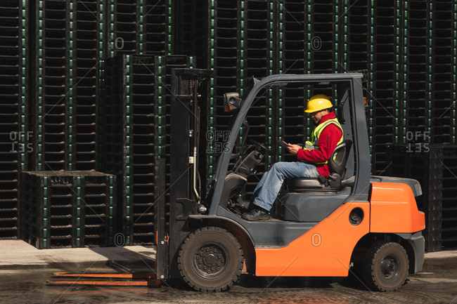 Side view of a middle aged Caucasian male factory worker sitting in a forklift truck using a smartphone beside stacks of pallets outside a warehouse at a factory