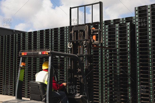 Rear view close up of a middle aged Caucasian male factory worker using a forklift truck to move a stack of pallets outside a warehouse at a factory