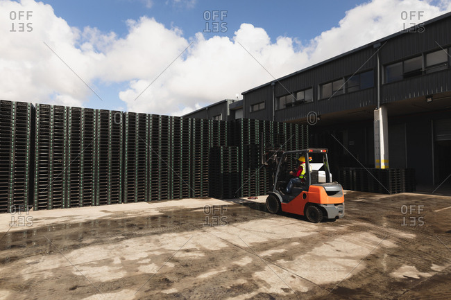 Rear view of a middle aged Caucasian male factory worker using a forklift truck to move a stack of pallets outside a warehouse at a factory