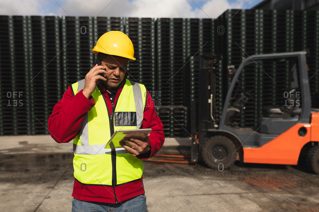 Front view close up of a middle aged Caucasian male factory worker on the phone using a tablet computer beside a forklift truck and stacks of pallets outside a warehouse at a factory