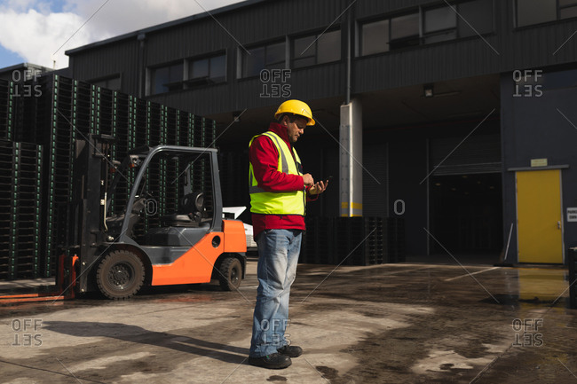 Side view close up of a middle aged Caucasian male factory worker using a smartphone standing beside a forklift truck and stacks of pallets outside a warehouse at a factory