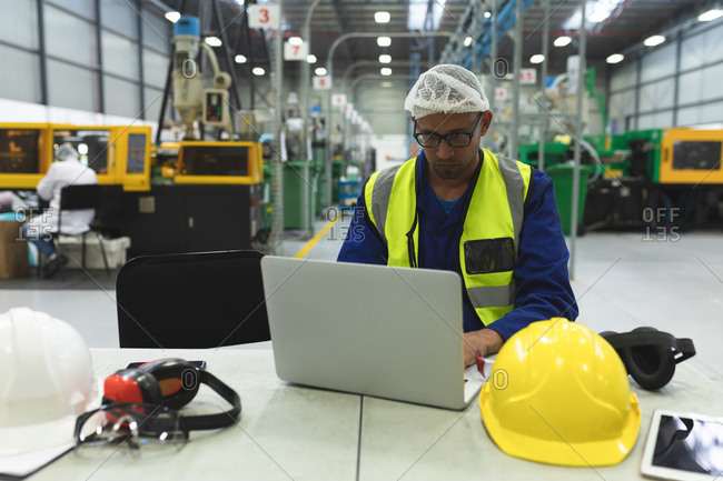 Front view close up of a middle aged mixed race male factory worker wearing glasses and workwear using a laptop computer in a warehouse at a factory processing plant