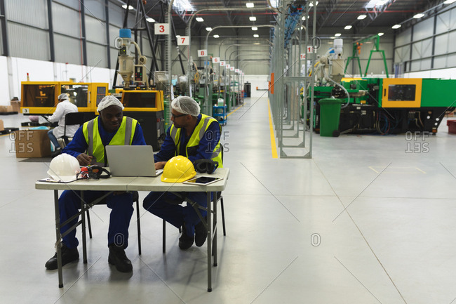 Front view of a middle aged mixed race male factory worker wearing glasses and a young African American male factory worker sitting at a table talking and using a laptop computer in a warehouse at a factory processing plant
