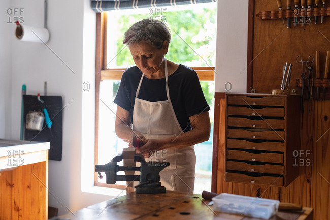 Front view of a senior Caucasian female luthier using a vice attached to a workbench in her workshop, with chest of drawers and window in the background