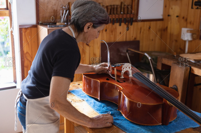 Side view of a senior Caucasian female luthier working on a cello on a workbench in her workshop, with tools hanging up on the wall in the background