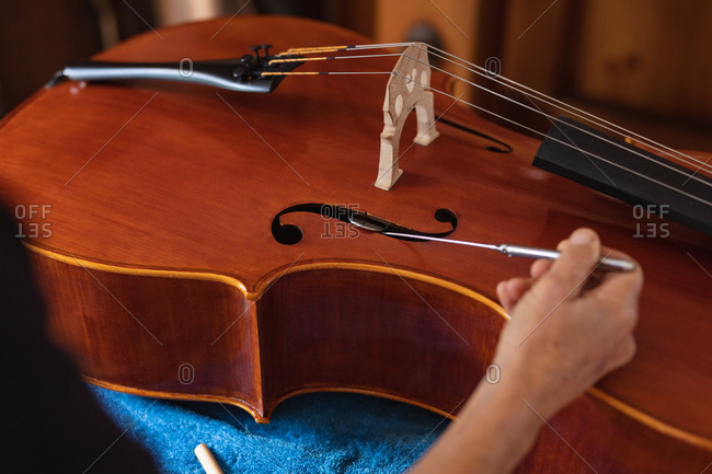 Close up of a senior Caucasian female luthier working on the body of a cello on a workbench in her workshop