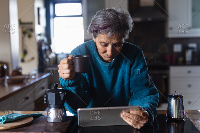 Front view of a senior Caucasian woman in a kitchen drinking coffee and using a tablet computer with kitchen cupboards in the background