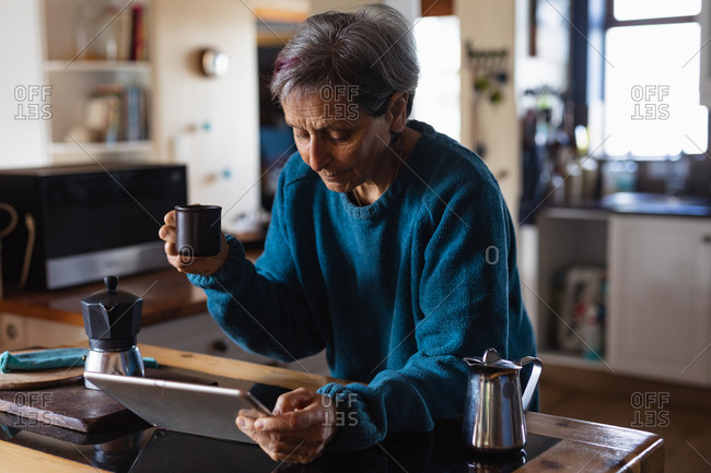 Side view of a senior Caucasian woman in a kitchen drinking coffee and using a tablet computer with kitchen cupboards in the background