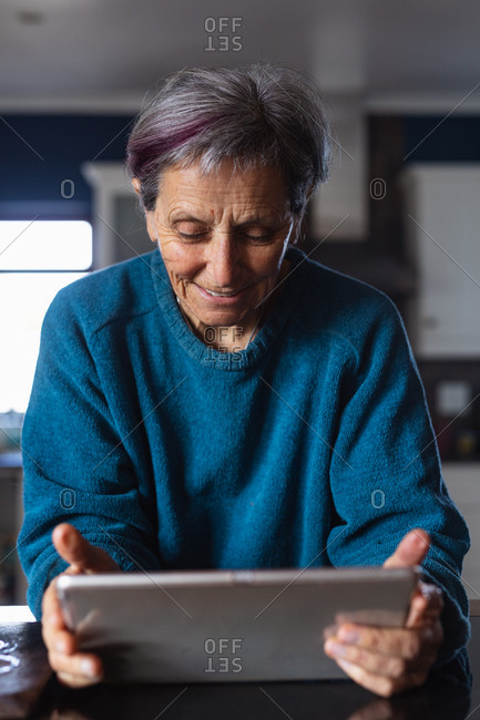 Front view close up of a senior Caucasian woman in a kitchen using a tablet computer