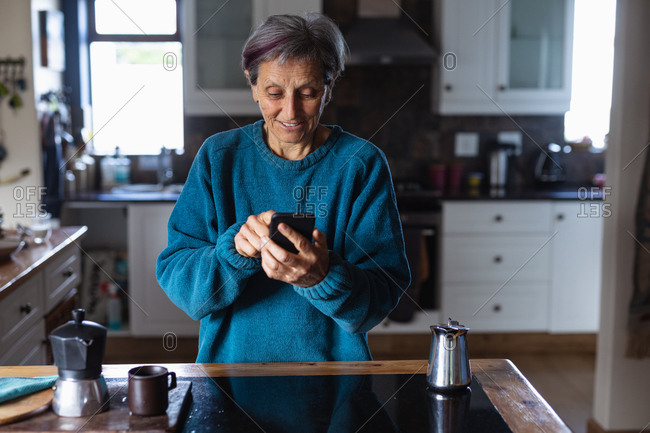 Front view of a senior Caucasian woman in a kitchen using a smartphone with kitchen cupboards in the background