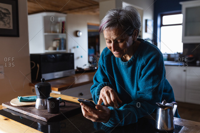 Side view close up of a senior Caucasian woman in a kitchen using a smartphone with kitchen cupboards in the background