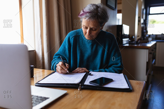 Front view of a senior Caucasian woman sitting at a table at home writing with a smartphone and laptop computer in front of her