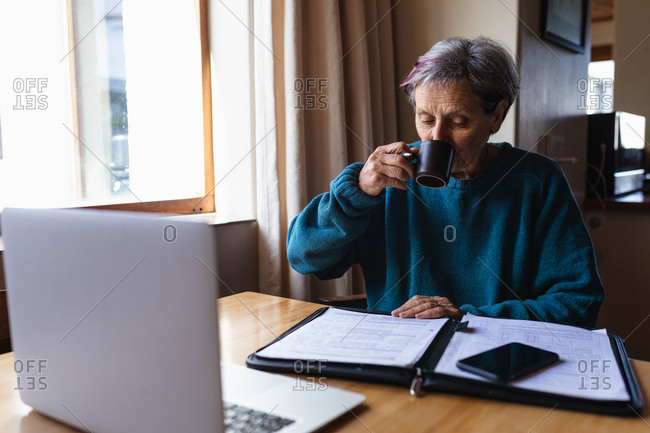 Front view of a senior Caucasian woman sitting at a table at home drinking coffee with a smartphone and laptop computer in front of her