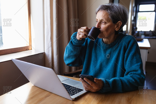 Front view of a senior Caucasian woman sitting at a table at home drinking coffee and holding a smartphone, with a laptop computer in front of her