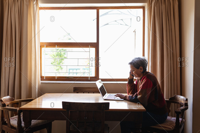 Side view of a senior Caucasian woman sitting at a table at home making a phone call and a laptop computer