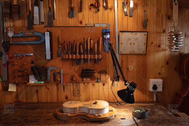 Violin being made in a luthier workshop with tools hanging up on the wall in the background