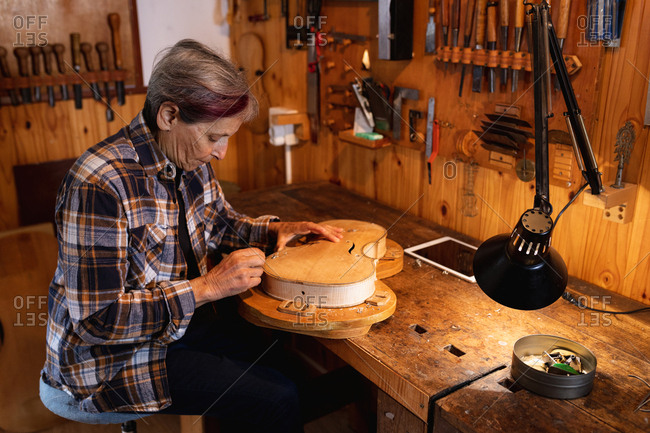 Side view of a senior Caucasian female luthier working on the body of a violin with a tablet computer on a workbench and tools hanging up on the wall in the background
