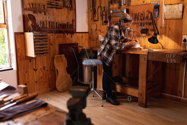 Side view of a senior Caucasian female luthier working on the body of a violin in her workshop, with tools hanging up on the wall in the background