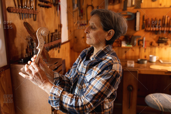 Side view of a senior Caucasian female luthier holding the scroll of a violin in her workshop, with tools hanging up on the wall in the background
