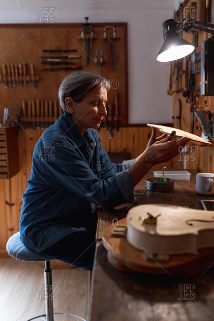 Side view close up of a senior Caucasian female luthier working on the body of a violin in her workshop, with tools hanging up on the wall in the background