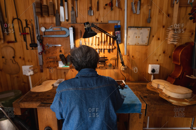 Rear view of a senior Caucasian female luthier working in her workshop, with tools hanging up on the wall in the background