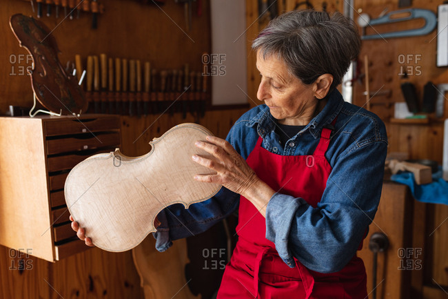 Front view of a senior Caucasian female luthier holding the body of a violin in her workshop, with tools hanging up on the wall in the background