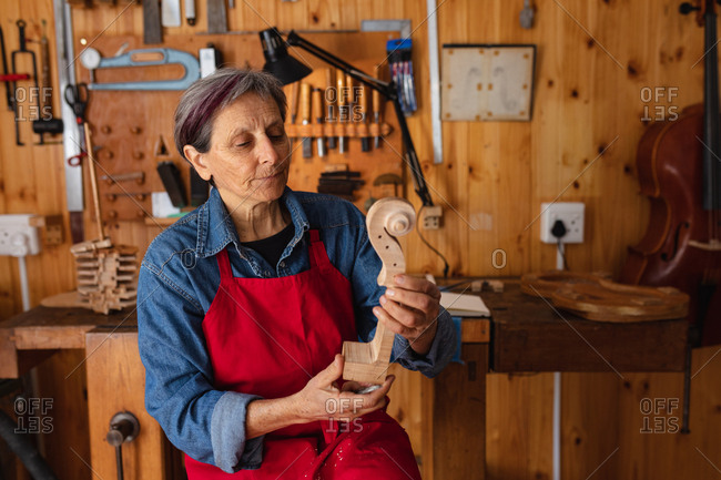 Front view close up of a senior Caucasian female luthier holding the scroll of a violin in her workshop, with tools hanging up on the wall in the background