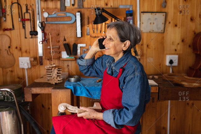 Side view of a senior Caucasian female luthier talking on the phone in her workshop with tools hanging up on the wall in the background