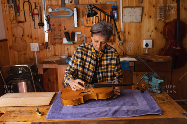Front view of a senior Caucasian female luthier working on the body of a violin in her workshop with tools hanging up on the wall in the background