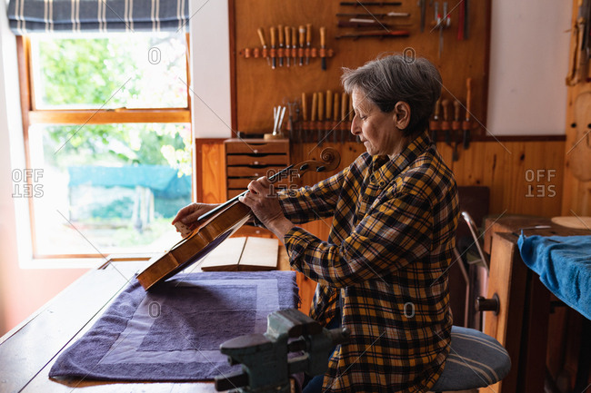 Side view of a senior Caucasian female luthier working on a violin in her workshop with tools hanging up on the wall in the background