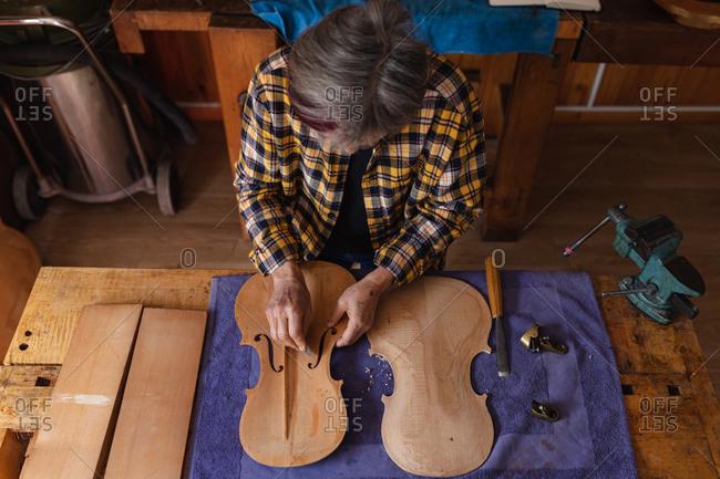 High angle view of a senior Caucasian female luthier working on the body of a violin in her workshop