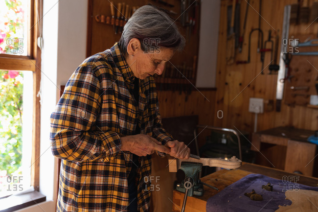 Side view of a senior Caucasian female luthier working on the scroll of a violin in her workshop with tools hanging up on the wall in the background